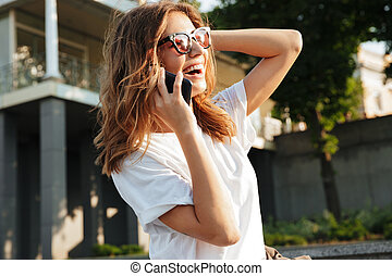 Image of beautiful happy woman wearing casual summer outfit and sunglasses, laughing while walking through city street and speaking on smartphone with smile