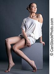 Image of beautiful leggy girl sitting on cube