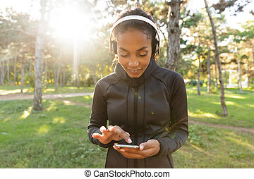Image of beautiful woman 20s wearing black tracksuit and headphones, using mobile phone while walking through green park