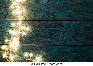 Image of blue wooden table with burning garland on side