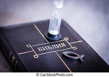 image of book Bible close-up in leather black binding with zipper with christian fish icon and hourglass on gray blurry background with black vignette