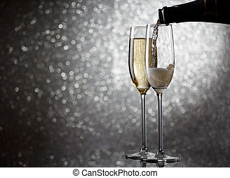 Image of bottle with pouring wine in wine glasses on gray background