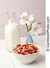 bowl of cereal with strawberries with bottle of milk