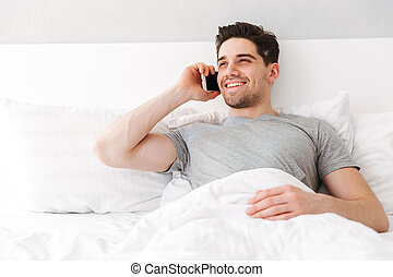 Image of brunette attractive man in casual t-shirt smiling while lying alone in bed with white linen, and talking on smartphone