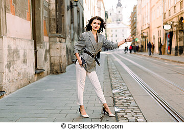 Image of brunette woman in stylish business clothes stopping taxi or car in the city street