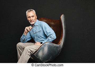 Image of businesslike gentleman 50s with grey hair and beard in glasses sitting on wooden armchair with meaningful look, isolated over black background