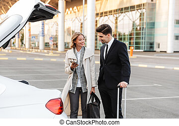 Image of businesslike man and woman standing with luggage by car