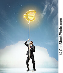 Image of businessman climbing rope attached to euro sign