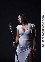 Image of busty slim singer posing in studio, on gray...