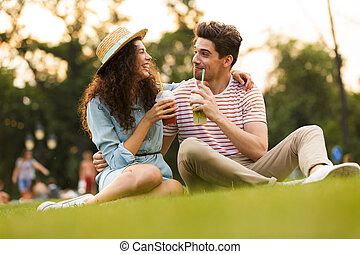 Image of caucasian couple man and woman 20s sitting on green grass in park, and drinking beverages from plastic cups