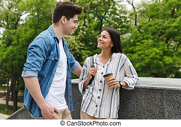 Image of caucasian couple with paper cup smiling and talking while standing on stairs outdoors