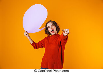 Image of caucasian girl holding thought bubble with copyspace while standing isolated over yellow background