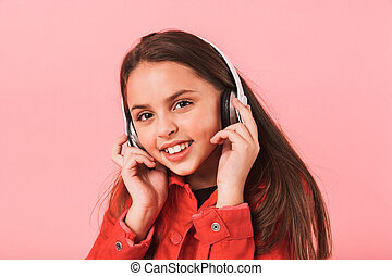 Image of caucasian little girl in casual wearing headphones listening to music, isolated over red background
