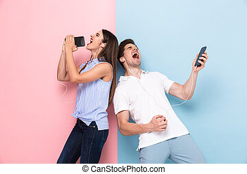Image of caucasian man and woman wearing earphones singing while listening to music on smartphones, isolated over colorful background