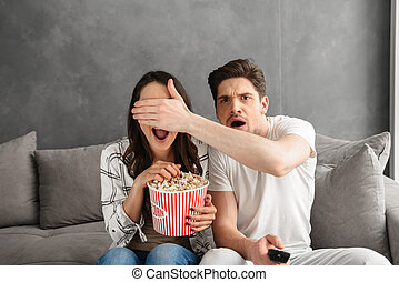 Image of caucasian uptight family sitting on sofa at home with popcorn in hand, while watching scary movie