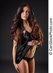 Image of charming brunette advertises underwear in studio