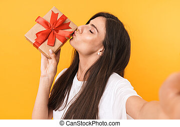 Image of charming brunette woman with long hair holding present box while taking selfie photo