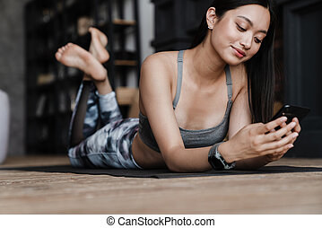 Image of cheerful asian girl using mobile phone while working out