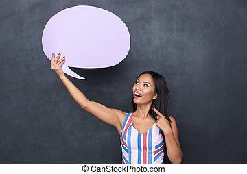 Image of cheerful asian woman 30s holding blank thought bubble above her head with copyspace for your text, standing isolated over gray background