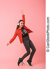 Image of cheerful little girl in casual wearing headphones dancing while listening to music, isolated over red background