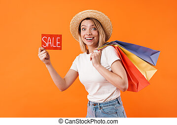 Image of cheerful woman holding shopping bags and sale banner