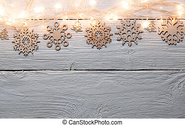 Image of Christmas wooden gray table with burning garland on top, snowflakes.