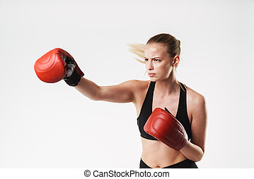 Image of concentrated blonde woman wearing tracksuit boxing with gloves while training