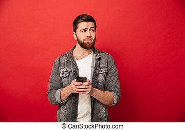 Image of Confused bearded man holding smartphone and looking away