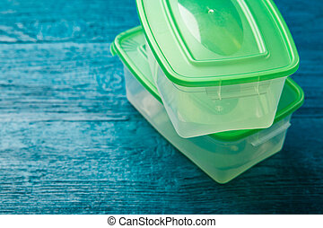 Image of containers for food with green covers on blue...