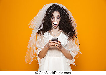 Image of creepy woman on halloween wearing wedding dress and scary makeup using cell phone, isolated over yellow background