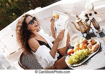 Image of curly woman having breakfast and reading newspaper on balcony