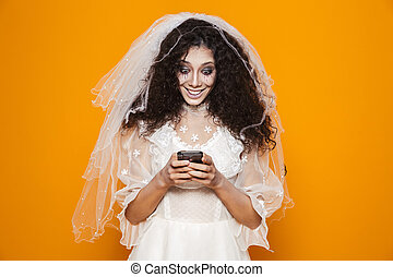 Image of dead bride zombie on halloween wearing wedding dress and scary makeup using cell phone, isolated over yellow background