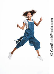 Image of delighted african american woman dressed in denim overalls jumping with thumbs up