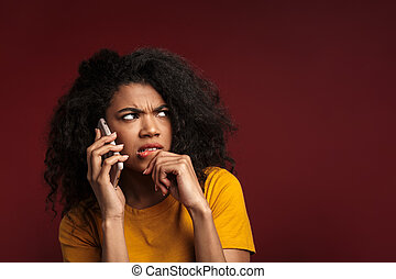 Image of displeased african american woman while talking on ...