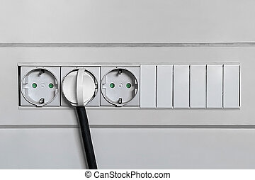 electrical plug is plugged into the wall outlet close-up