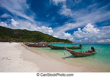 Image of empty long tail boat on tropical beach. Clear water...