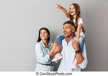 Image of european happy family woman and man smiling and looking aside while daughter sitting on the neck of her father, isolated over gray background
