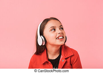 Image of european little girl in casual wearing headphones listening to music, isolated over red background