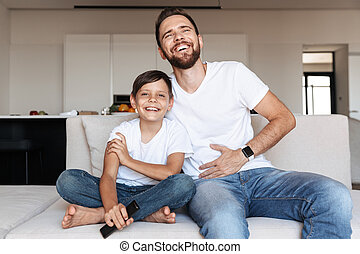 Image of european man 30s and boy 8-10 laughing, while sitting on couch indoor with remote control