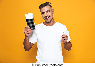 Image of european man 30s in white t-shirt holding credit card and travel tickets