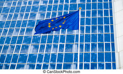 Image of European Union flag with staras over blue background against big modern office building. Concept of ecenomy, development, government and politics