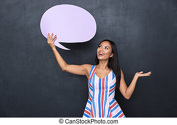 Image of excited asian woman 30s holding blank thought bubble above her head with copyspace for your text, standing isolated over gray background