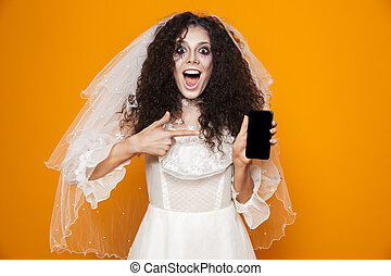 Image of excited zombie woman on halloween wearing wedding dress and holiday makeup using cell phone, isolated over yellow background