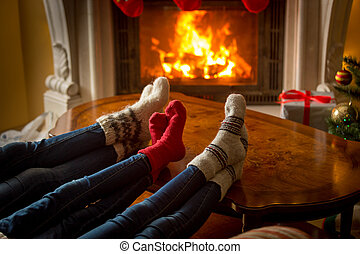 Image of family feet in woolen socks resting next to the burning fireplace