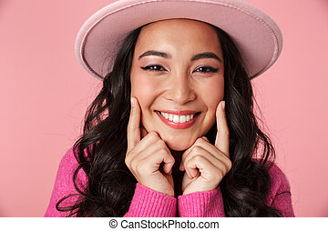 Image of fashion asian girl wearing hat showing her smile with fingers