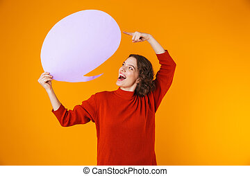 Image of feminine girl holding thought bubble with copyspace while standing isolated over yellow background