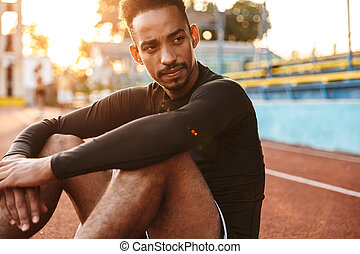 Image of focused african american man sitting at sports ground outdoors