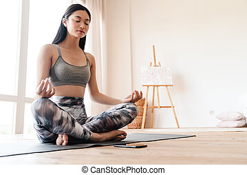 Image of focused asian girl using mobile phone while meditating