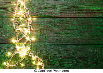 Image of green wooden table with burning garland on side