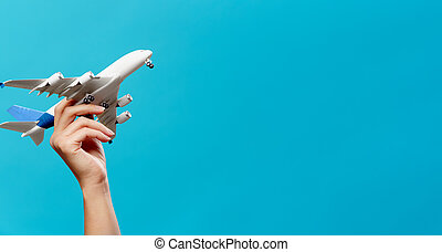 Image of hand with airplane on empty blue background in studio